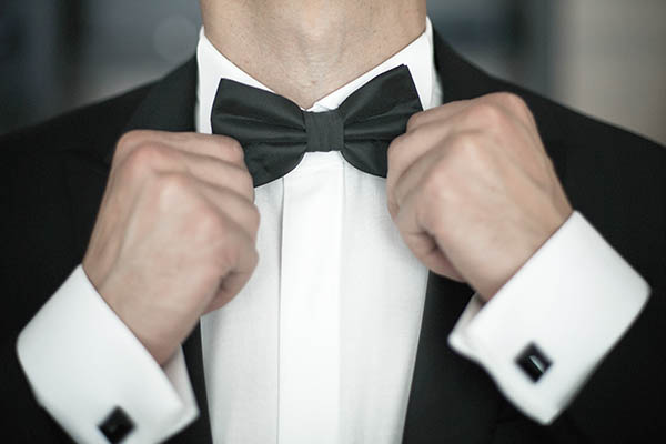 Close up of a man tying his bow tie, finishing up his black tie ensemble.