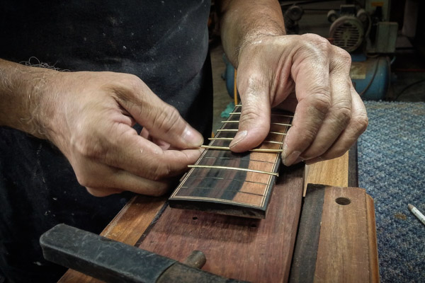 A luthier placing the frets on a guitar