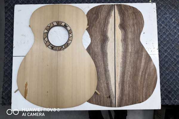 Pieces of wood cut out to the shape of a guitar by a luthier