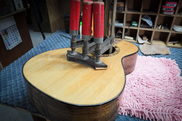 weights holding down guitar body as it is being binded
