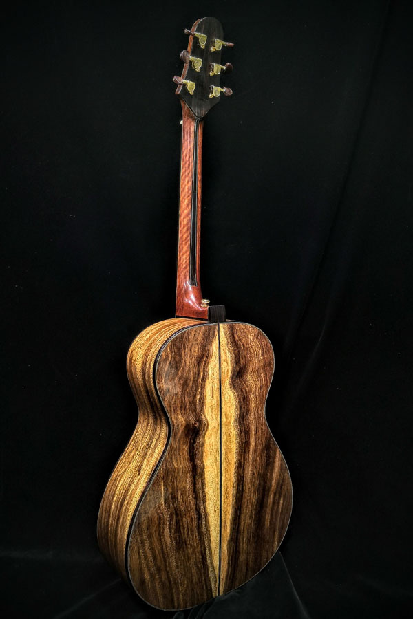 beautiful guitar standing up facing back made by a luthier