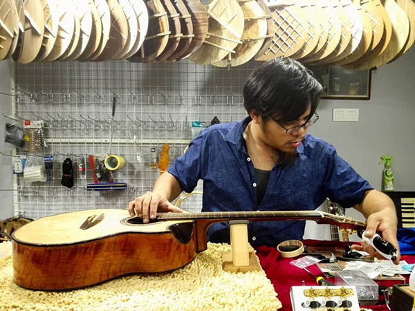 Jonathan Woo, a luthier working on one of his guitars