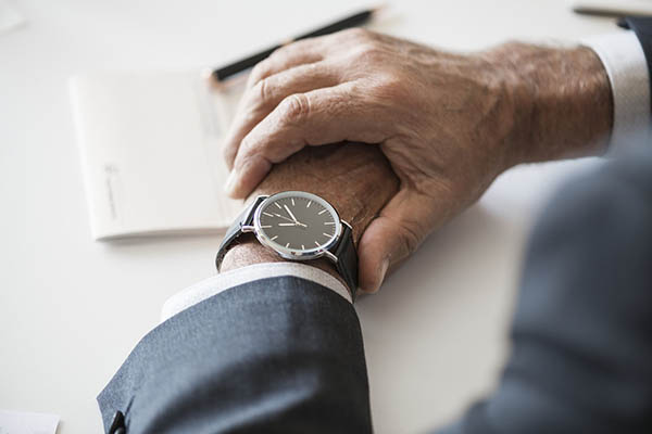 A gentleman taking a look on his wristwatch in a business meeting.