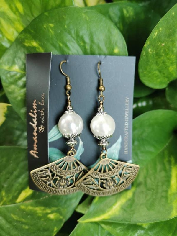 a pair of pearl and charm earrings. handmade accessories