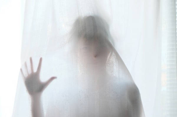 The Cheapoholic predicament; a figure behind a white curtain.