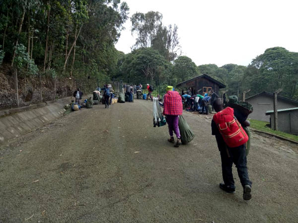 The porters are seen weighing and arranging the bags before carrying them to the next camp.