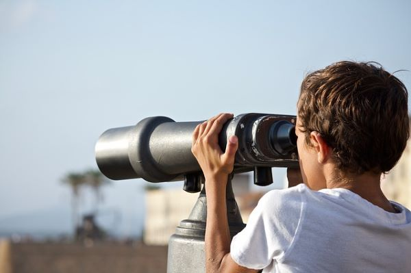 Young boy looking through a large binoculars, Family needs to be in on retirement plans.