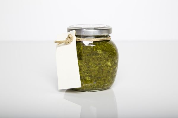 Unlabeled jar filled with green pesto. An indication of homemade products or even services so easily sold online.