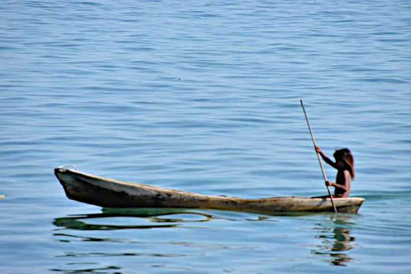 The citizenless Bajau Laut child paddling a rickety boat as a routine in Mabul.