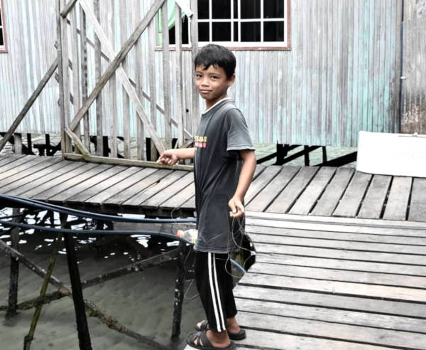 A local boy seen fishing within the gaps of the stilt houses in Mabul.