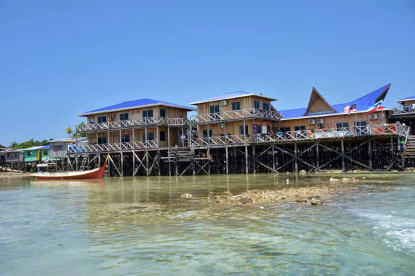 After 45 minutes on a rocky boat, a blue-roofed wooden stilt house began to loom as the boat moored to the pier side in mabul.