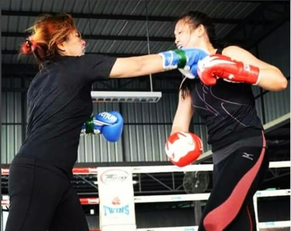 She is sparring in the ring for a boxing competition.