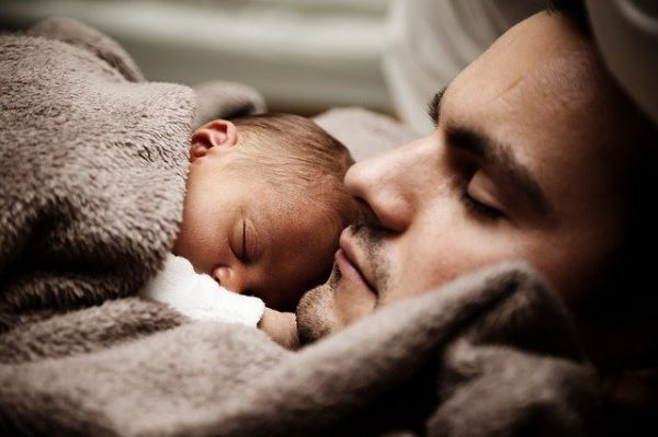 Father coddling his newborn while they both sleep. Fathers now play a very active role in childbirth care.