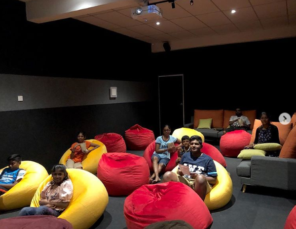 People at CineboxPD enjoying a movie on bean bags in the cinema.