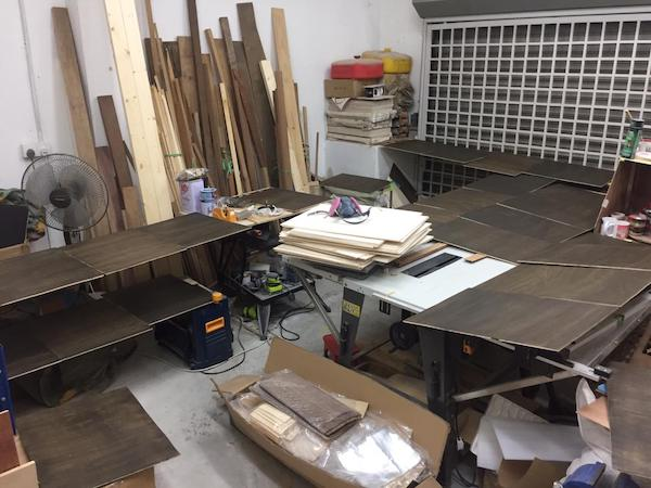 Plywood laid out to dry after staining work in the garage at writer Atiqah's part time job.