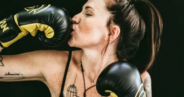 A woman kisses her boxing gloves enthusiastically.