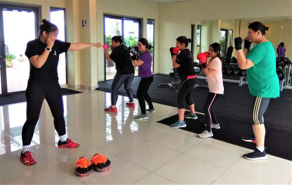The coach is teaching her students how to execute a jab in boxing.