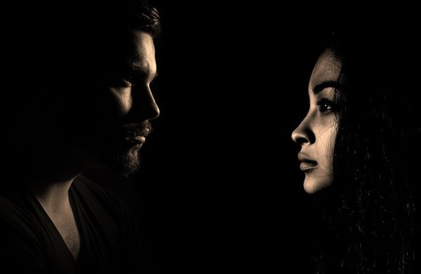 A man and a woman look at each other against as dark background. Men and women are both emerging as important players in fields they never were before.