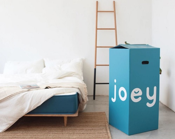 The Joey Mattress displayed next to the box they package the mattress in
