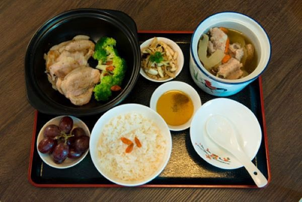 childbirth; a full set meal consisting of a bowl of rice, a bowl of chicken and vegetable soup, steamed chicken, vegetables and grapes, arranged nicely on a tray.
