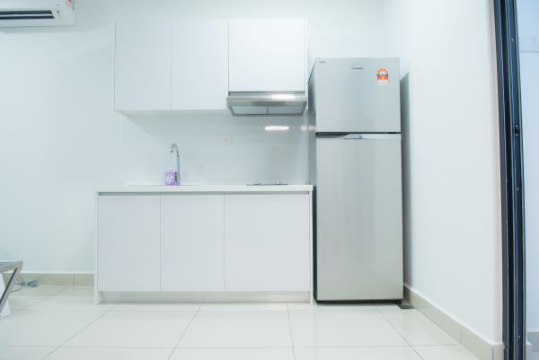 Simple kitchen furnished with fridge, top and bottom kitchen cabinet, small stove and hood.