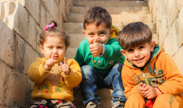 Three siblings on the stairs at Aaqrabâte, Syria