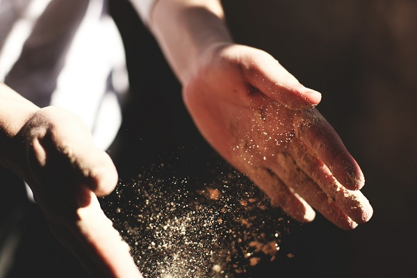 Dust on a person's hand. Don't let the dust collect inside your mattress!