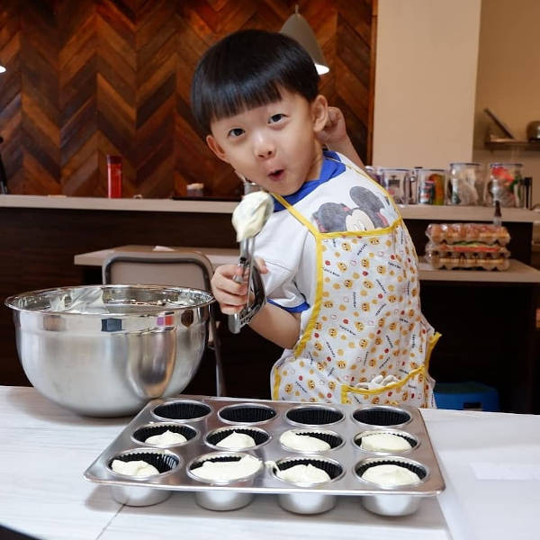 Little boy having fun with cupcake batter in baking classes