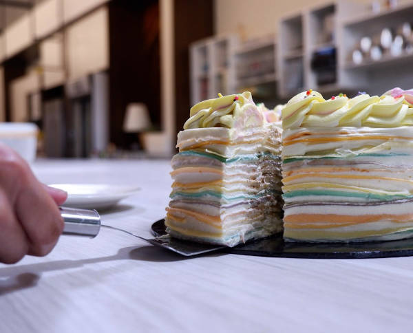 Hand takes a slice of multi-coloured layered crepe cake