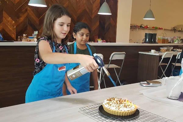 Girl holding torch over her freshly baked meringue