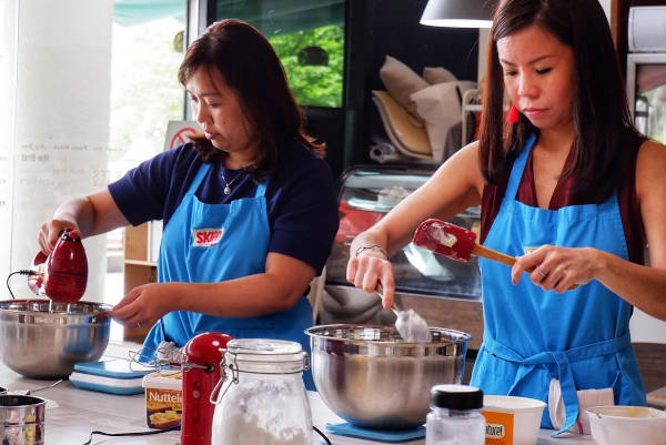 Ladies reaping the benefits of kitchen therapy while preparing cake batter