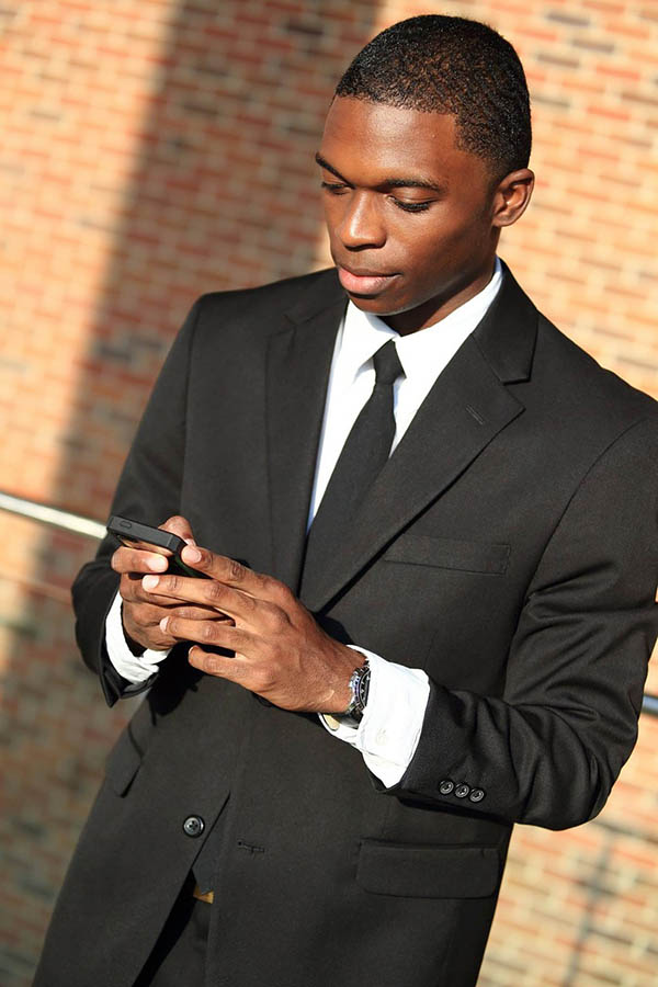 """A gentleman wearing what he believes is the """"standard"""" black suit, with a white shirt and black tie."""