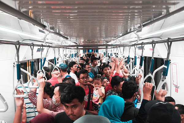 An image of the inside of a train during rush hour, with passengers being packed together tightly.