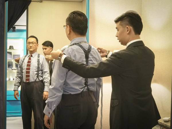 Tailor measuring up a customer for a bespoke suit, looking towards a full-length mirror to the front.