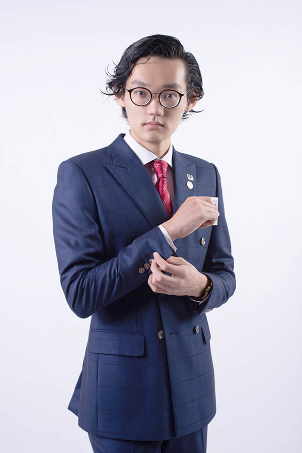 Three quarter body portrait of Sky Ng, wearing a double breasted suit, navy blue with faint window pane weave pattern.