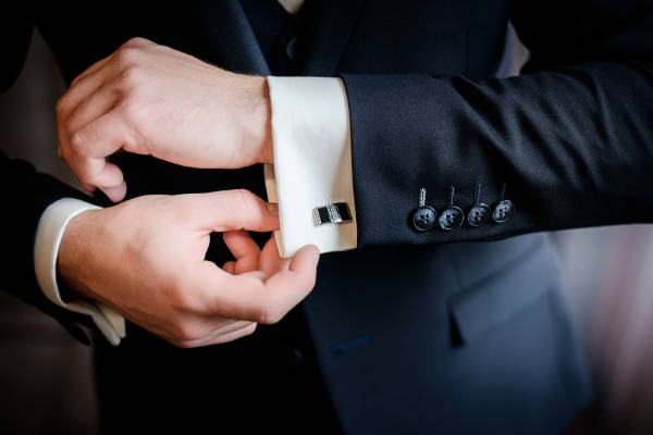 Close up of a gentleman subtly adjusting his shirt cuffs under his jacket sleeves.