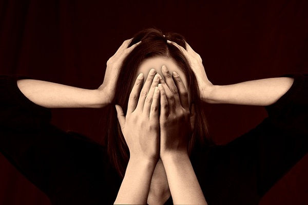 A woman with social anxiety with hands covering her face.