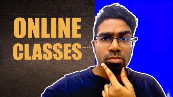 """Mr Ruel stands in front of a board brandishing """"Online Classes"""""""
