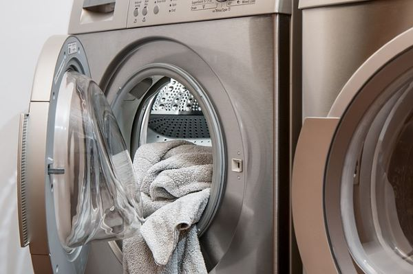 washing machine with a wet towel protruding from it.
