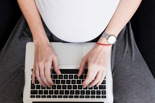 pregnant mother sitting down with a laptop on her lap researching for her newborn