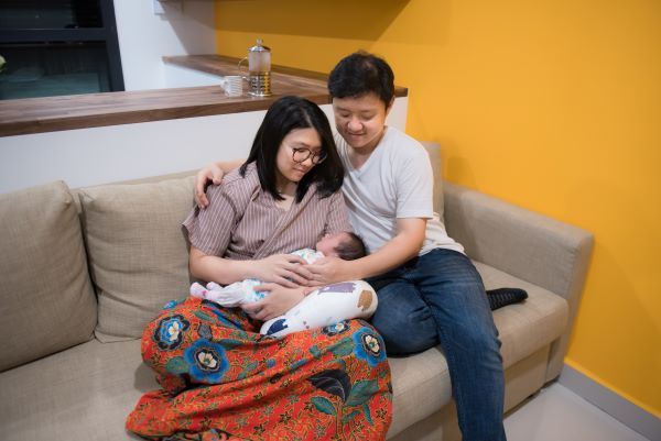a mother cradling her newborn with the father beside her. Newborns