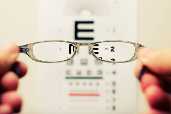 Determine the clarity of your vision with glasses as you view the eye test chart.