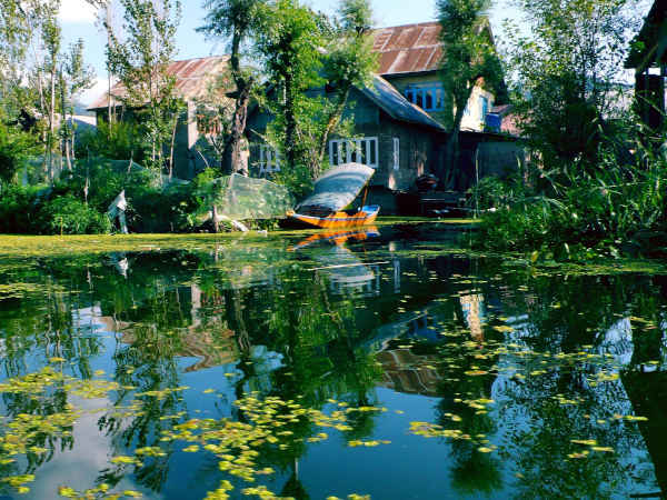 Reflection of a house on Dal Lake, Kashmir, on a sunny day.
