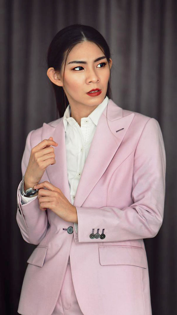 Woman wearing a pink suit and white shirt.
