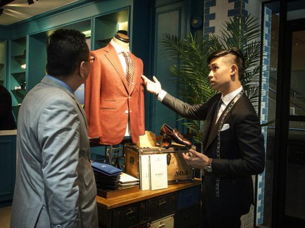 Tailor explaining about a suit to a client
