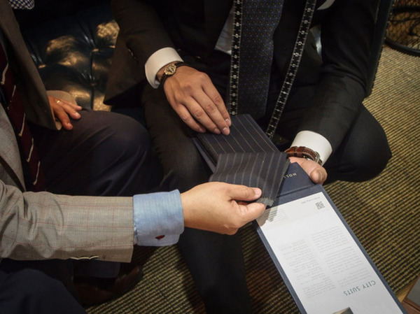 Inspecting fabric swatch for a bespoke suit