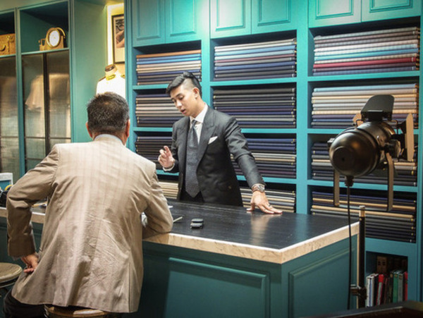 Tailor and client discussing about  suit