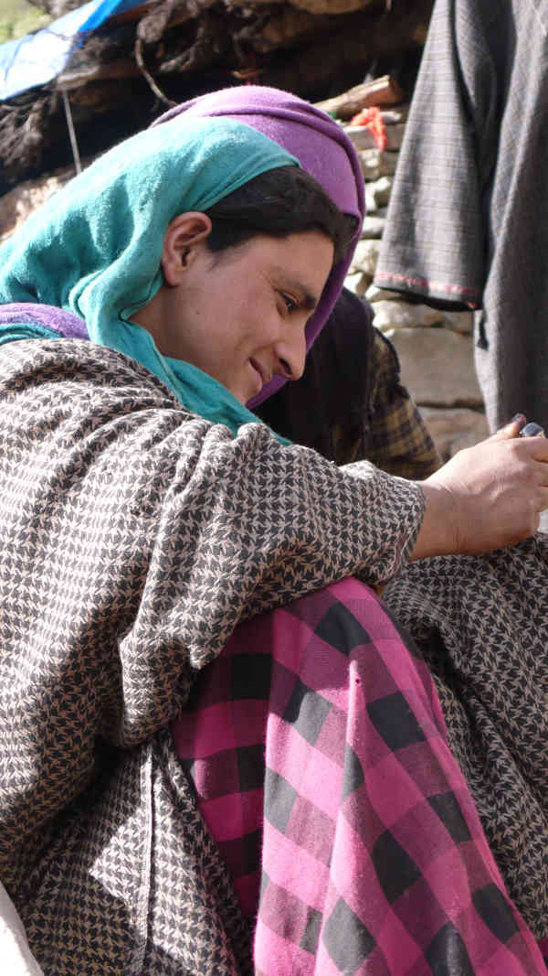 Beauty is in the eye of the beholder - a young Gujjar lady looking at her photo on the mobile phone.