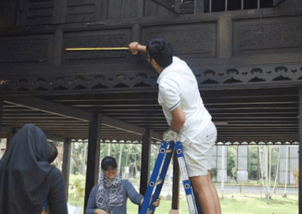 A photo of Atiqah's team member measuring the outside part of the house by standing on a ladder.