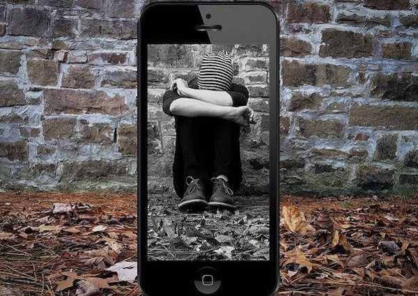 Cyberbullying: A photo of a teenager behind a phone showing how the dark side of social media and the internet.